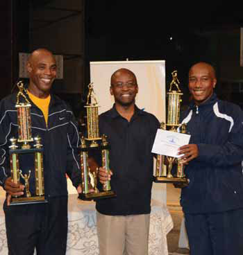 Julian White (left) and Mark Griffith (right) pose with their trophies and Minister of Sport Stephen Lashley.