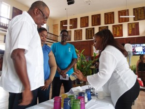 Subrina Hinds (right) of Blue Star Therapies, shows a product to Minister of Health John Boyce. Second from left is Barbados Reiki Association vice-president Sonia Johnson, and president Sharon Hurley Hall (third left).