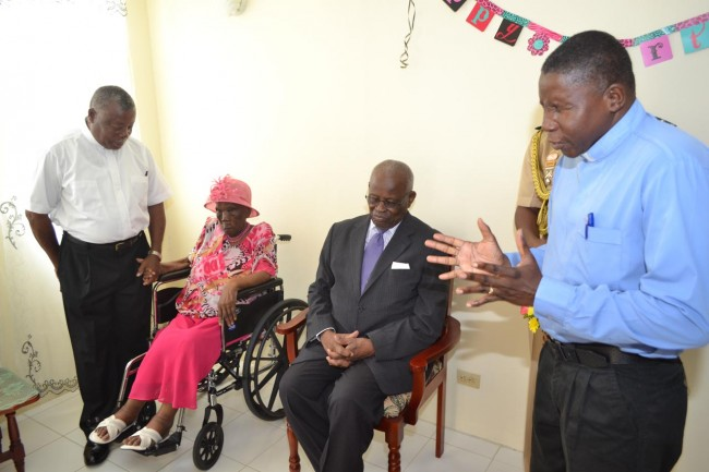 Governor General Sir Elliott Belgrave (second from right), centenarian Marguerita Jones (second from left) and her son-in-law Reverend Alvin St. Hill (left) listening as Reverend Andrew Roberts (right) prays.
