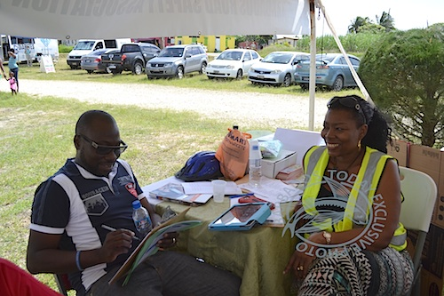 MP Dwight Sutherland taking the written road safety test, while Sharmane Bowen, president of the Barbados Road Safety Association looks on.