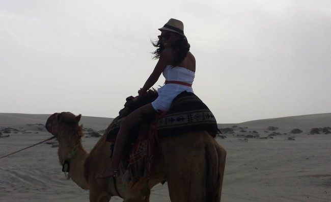 Charmaine riding a camel in the Qatari desert.