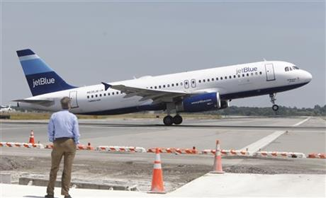 A man watches a JetBlue airplane take off from John F. Kennedy International Airport in New York.