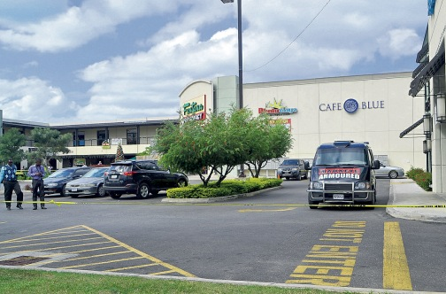 Police at the scene of a robbery at Farview Shopping Centre in Montego Bay yesterday.
