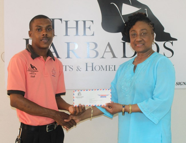 Dr Donna Hunte-Cox handing over a monetary donation to Kemar Saffrey.