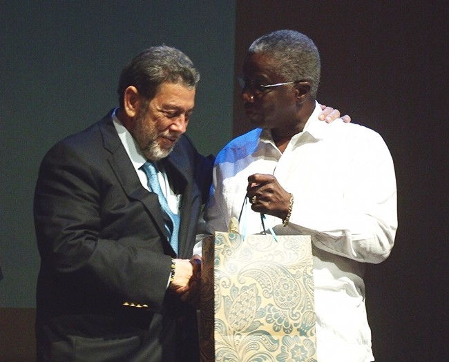 St Vincent's Prime Minister Ralph Gonsalves receiving from Prime Minister Freundel Stuart, a book of Mirror Image Lectures to commemorate the work of Errol Barrow, edited by Ronald Jones.