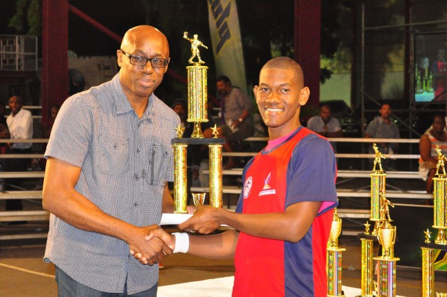 The National Sports Council's interim CEO Jerry Blenman presenting Under-21 champion Emar Edwards with his trophy.