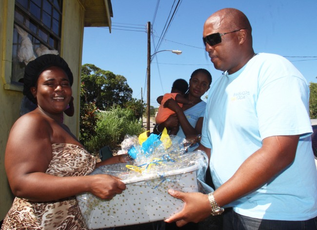 Dione Fagan had her hands full receiving her gift from Barbados Today's Sales and Marketing Manager David Williams.