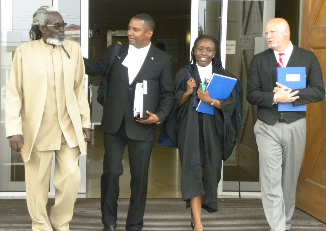 Wilfred Abrahams (second from left), lawyer for sport shooters, leaves the High Court today with client Bernard Chase (left) and assistants Sukeena Maynard and Bryan Weekes.