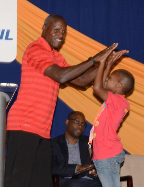 Carl Lewis makes this young athlete's day with a 'high five'.
