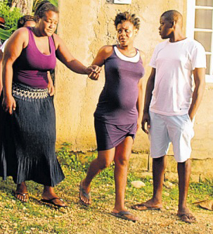 Thirteen-year-old Shawn Clayton's mother (left) being assisted by community members.