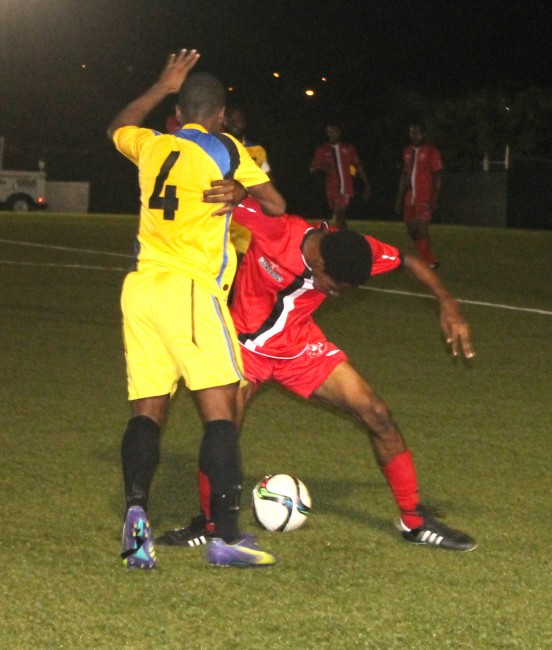 UWI goal scorer Jomo Harris (No.4) tries to hold off a strong challenge from Jabarry Greenidge of Brittons Hill.