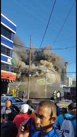 Curious onlookers gathering as fire guts the Hearty Foods supermarket compound in Arima earlier today.