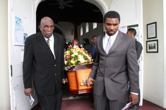 """Pall-bearers take the mortal remains of Evelyn """"Granny"""" Walcott to its final resting place."""