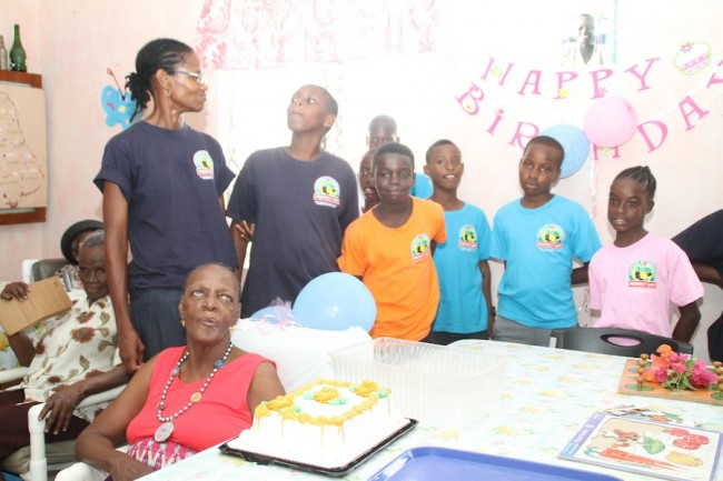 Campers engaging in birthday celebrations with one of the Geriatric Hospital Day Care clients.