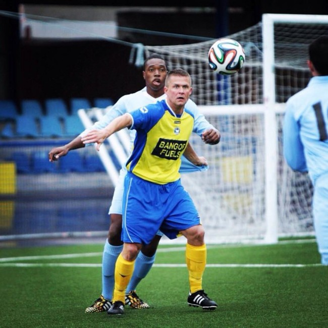 Ranaldo Bailey defending against Bangor FC's  Andy Morrow during  a pre-season friendly.