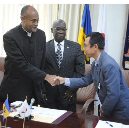 Minister of State in the Office of the Prime Minister Patrick Todd (left) and Second Secretary at the Japanese embassy Takafumi Ura shake hands to celebrate the installation of the solar photovoltaic systems while Minister of Education Ronald Jones looks on.