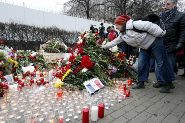 A woman puts flowers near the French embassy to commemorate victims of the Paris attacks, in Moscow, Russia, November 14, 2015. REUTERS/Maxim Zmeyev