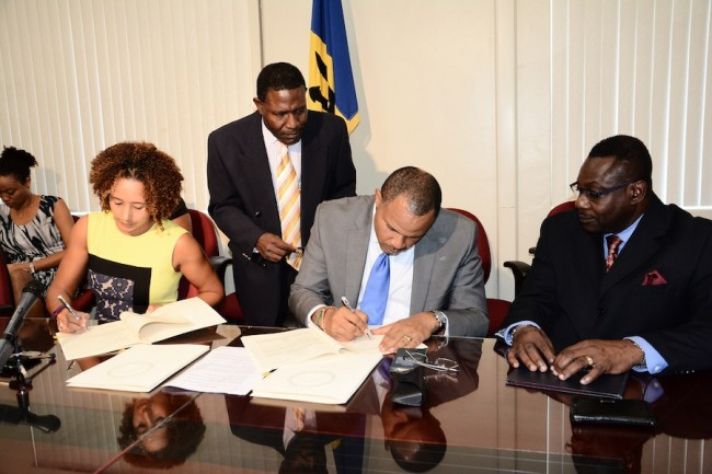 Minister of Finance and Economic Affairs, Christopher Sinckler, and Chief of Operations and Officer in Charge of the Inter-American Development Bank in Barbados, Christel Saab, signing the loan agreements, while Minister of Social Care, Steven Blackett, looks on.