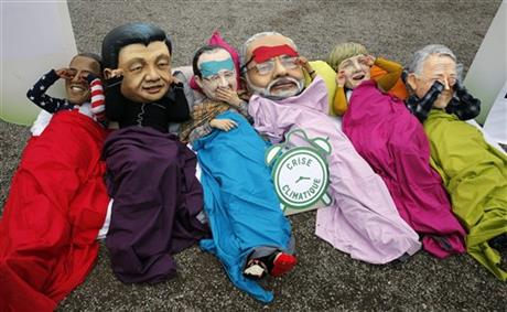 Oxfam activists wearing masks of, from left, America's President Barack Obama, China's President Xi Jinping, France's President Francois Hollande, India's Prime Minister Narendra Modi, German Chancellor Angela Merkel and Australia's Prime Minister Malcolm Turnbull as they staged a protest during the COP21, United Nations Climate Change Conference in Le Bourget, north of Paris,