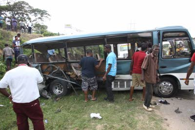 People looking at the wreck of the tour bus from which a passenger died in yesterday's road crash in Trelawny.