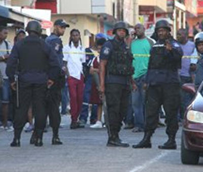 Police officers securing an area where curious onlookers gather on Mucurapo Street, San Fernando, near the scene of the killing of Michael Patterson.