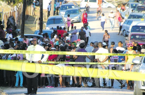 People watch from behind police caution tape as investigators probe the deaths on Thursday of Gail Anderson and her common-law husband John Williams.