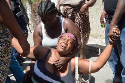 A woman, identified as the grandmother of ten-year-old Nhyeema Barrett, who perished in the fire, is consoled by friends.