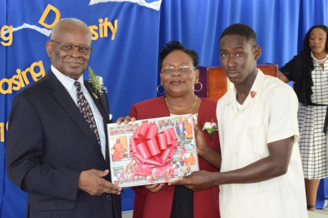 Governor General Sir Elliott Belgrave receiving a gift from student Shaquone Hoyte as principal Wendy Blackman looks on.