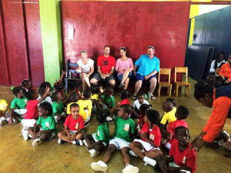 (From left) Lindsay and Mick Guymon and their friends Kim and Steve Holt with the students at Hammersmith Preparatory