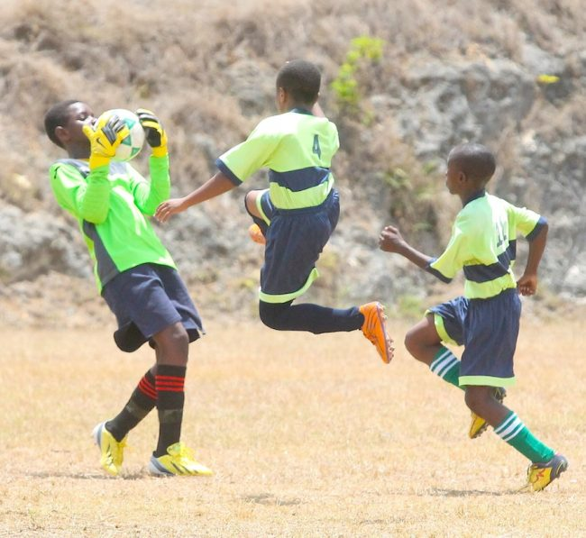 Good Shepherd's goal-scorer James Pounder (center) challenges St Silas Primary's goalkeeper Malique Griffith for the ball.