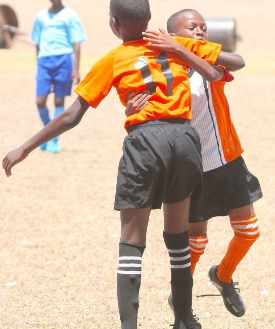 Omari Haynes  celebrates with his teammate after scoring Bayley's Primary's fifth goal against St Mark's Primary.
