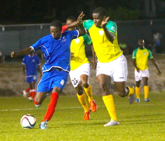 Renaldo Bignall of Empire puts Barbados Defence Force Sports Programme defender Kemar Chase under pressure.