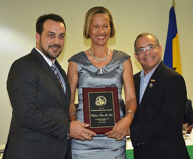 Professor Dr Anne St John posing with her plaque received from Rotary West. At left is Rotary West president Farid Mansoor, at right, Rotary District Governor Milton Inniss.