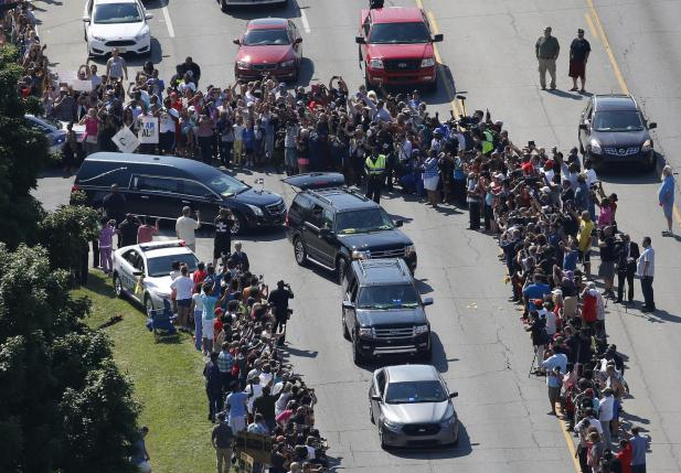 The hearse (center, L) carrying the remains of Muhammad Ali leaves the A D Porter & Sons funeral home during the funeral procession for the three-time heavyweight boxing champion in Louisville, Kentucky, U.S., June 10, 2016.   REUTERS/Adrees Latif