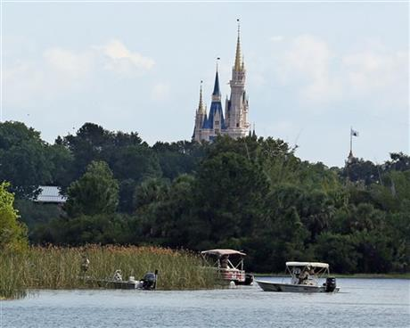 In the shadow of the Magic Kingdom Florida Fish and Wildlife Conservation Officers search for the body of a young boy Wednesday, June 15, 2016 after the boy was snatched off the shore and dragged underwater by an alligator Tuesday night at Grand Floridian Resort at Disney World in Lake Buena Vista.