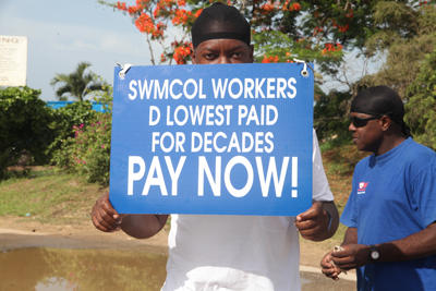 A SWMCOL worker holds up a plackard during the workers protest outside the Beetham Landfill Monday.