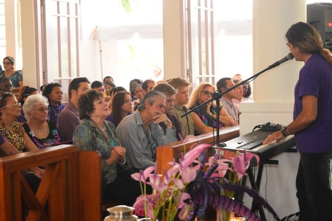 From left at front: Renee Ratcliffe's aunt Valerie van der Meulen-Sheppard, father Peter Sheppard, twin sons Harrison and Nicholai and mother Neilsa during the thanksgiving service, as her uncle Alan Sheppard sings The Dragonfly which he penned for his niece.
