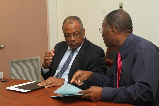 Minister of Health John Boyce (left) in conversation with Permanent Secretary in the Ministry of Health Tennyson Springer during today's news conference.