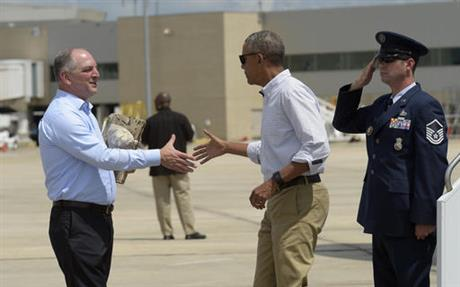 President Barack Obama reaches to shake hands with Louisiana Governor John Bel Edwards, after arriving on Air Force One at Baton Rouge Metropolitan Airport in Baton Rouge, Louisiana.