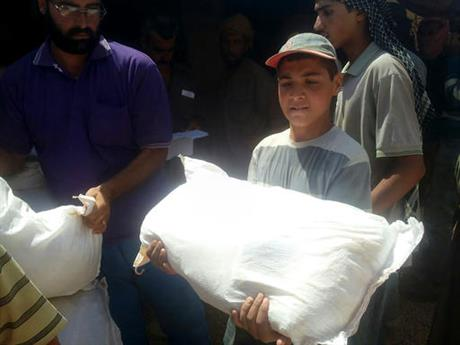 A boy holds a sack of food aid after aid agencies dropped via crane food across the Jordan-Syria border to community leaders charged with distributing equitably the supplies to the 64,000-person refugee camp called Ruqban on Thursday.