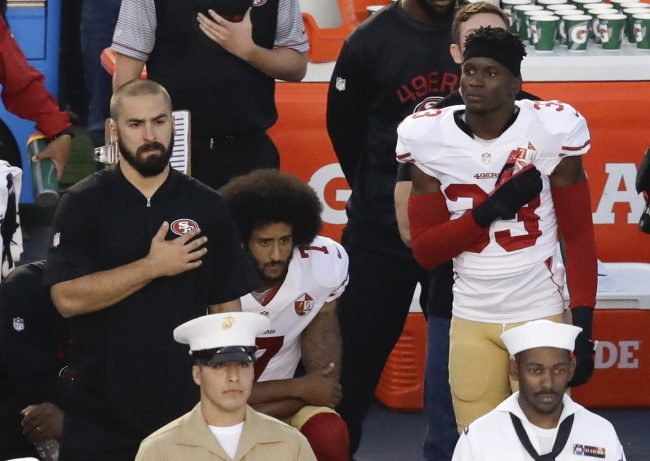 Colin Kaepernick (with afro hairstyle) sitting during the playing of the United States' national anthem.