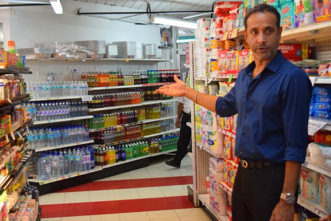 Manager at Mall Mart Nirmal Thani points to bottles of water, a hot seller today.