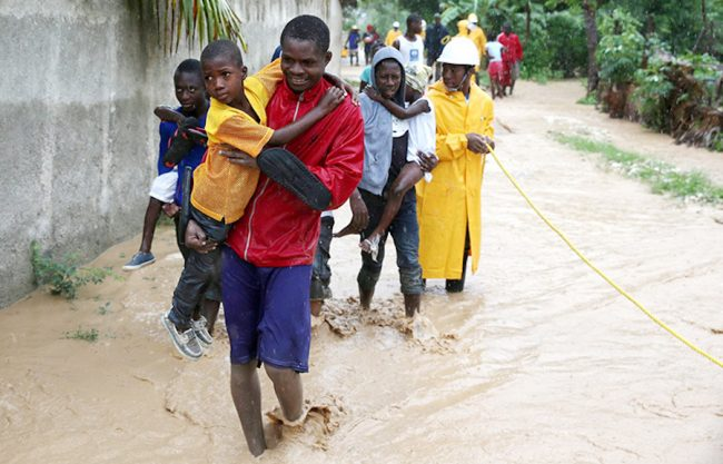 Haitians wading through flood waters.