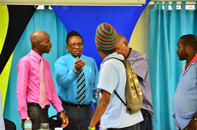 NUPW Acting Assistant General Secretary Wayne Walrond (left) and other officials in an animated discussion with at least one SSA worker this afternoon.