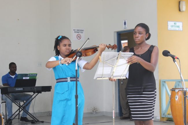 Viola Shanice Barker of the Alexandra Secondary School being assisted by Ronette Rouse.