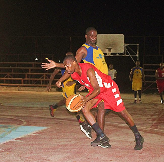 Javid Beckles (with ball) of Warrens gets past Dover's big man Ryan Lewis.