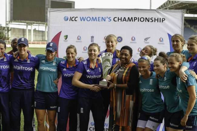 Heather Knight receives series trophy from Jamaica Minister of Sports Olivia Grange, while surrounded by her teammates.