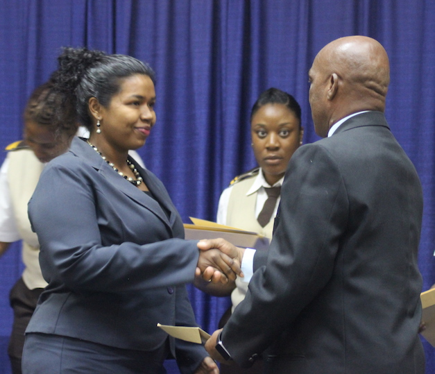 Shavana Allder (left) collects her certificate  of induction from immigration officials.