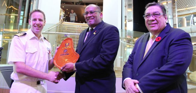 Minister of Tourism Richard Sealy presenting the traditional Barbados mahogany plaque to Captain John Westgarth-Pratt, while Chairman of Barbados Port Inc. David Harding looks on.
