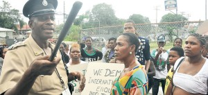 Tivoli Gardens residents listen to a policeman outside of the Police Officers' Club, in Kingston yesterday.
